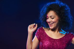 Closeup of happy mixed race woman in sequined dress dancing on a party over dark background