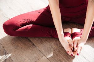 Closeup of hands and legs of young woman doing yoga barefoot