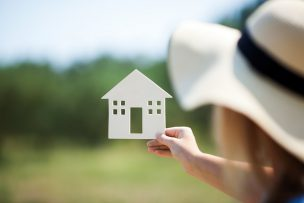 Woman in summer hat holding small house model outdoor. Defocused green nature scene in background. Real estate, mortgage, eco or country house concept